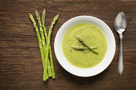 Fresh asparagus soup on wooden background overhead shoot