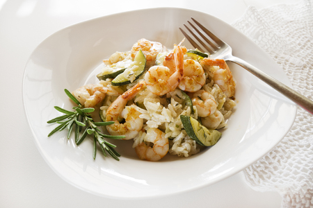 Risotto with fresh shrimps and vegetables on white table.