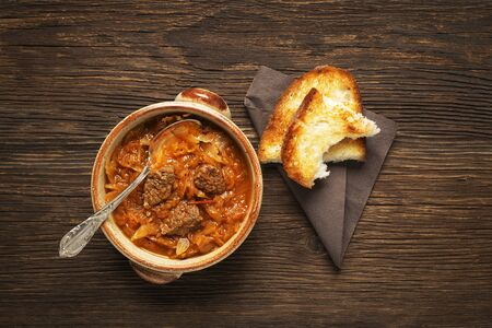 goulash: Goulash cabbage with beef on wooden background.