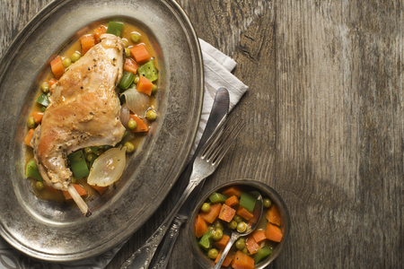baked: Roast rabbit leg with stewed vegetables on wooden table. Stock Photo