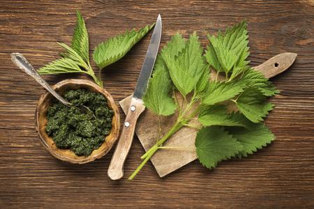 nettle: Nettle fresh green leaves on a wooden background.
