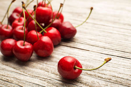 drupe: Fresh cherries on wooden table close up.
