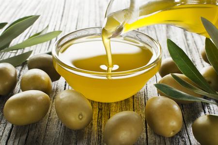 Fles gieten olijfolie in een kom close-up