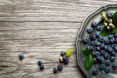 wildberry: Juicy and fresh blueberries with green leaves on rustic table