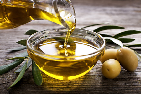 Bottle pouring virgin olive oil in a bowl close up 스톡 콘텐츠