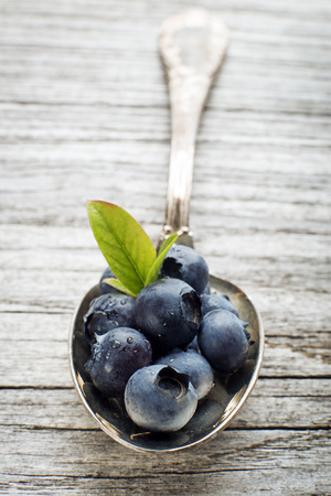 wildberry: Juicy and fresh blueberries with green leaves on spoon close up Stock Photo