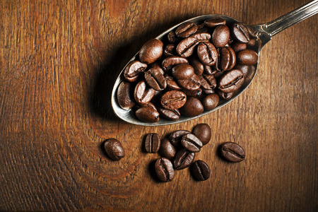 tropical shrub: Coffee beans in spoon on wooden background.