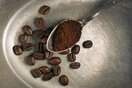 bush bean: Fresh ground Coffee in spoon on wooden background.