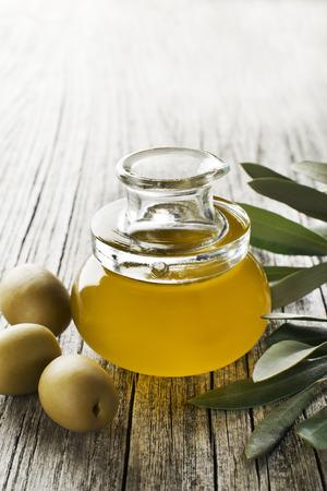 aceite de oliva: El aceite de oliva en una botella en una mesa de madera