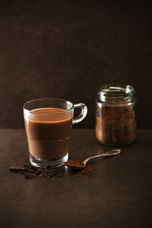 glass background: Cup of hot chocolate with cocoa powder and pieces of chocolate.