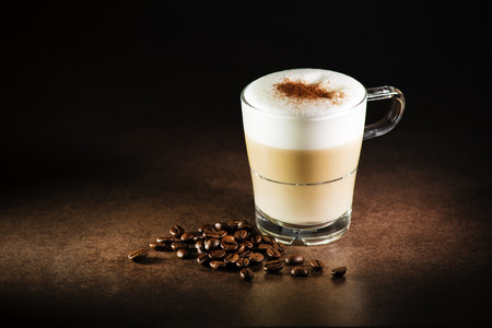 Cup of hot Cappuccino Coffee on dark background.