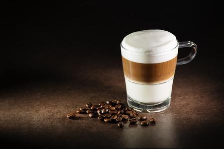 ホットのラテ マキアート コーヒーのガラスをクローズ アップ