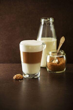 glass cup: Glass of hot Latte macchiato coffee on dark background Stock Photo