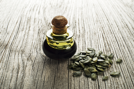 Dark pumpkin oil with seeds on wooden background Stock Photo