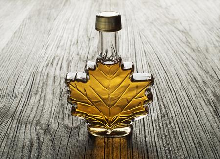 jarabe: Jarabe de arce en botella de vidrio en la mesa de madera