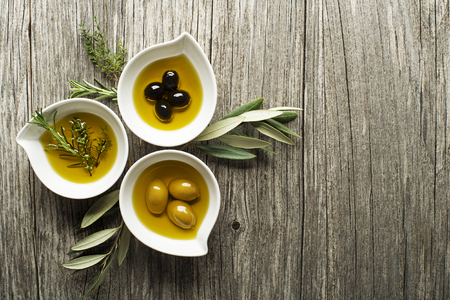 Olive oil with fresh herbs on wooden background Archivio Fotografico