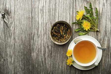 Cup of healthy dandelion tea on wooden background. Herbal medicine.