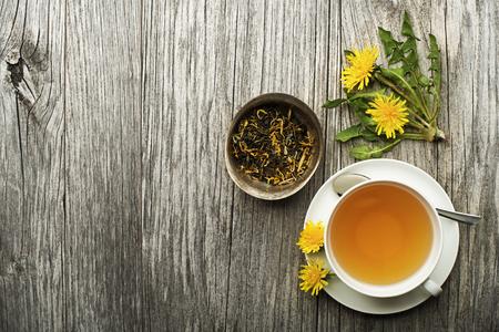 Tazza di tè sano dente di leone su sfondo di legno. Medicina a base di erbe.
