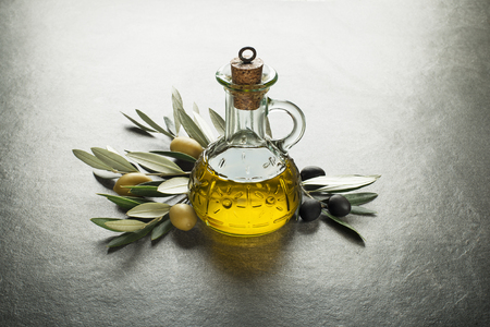 maturation: Olive oil and olive branch on the gray table Stock Photo