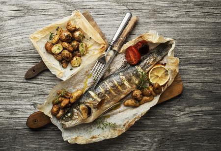 나무 테이블에 구운 감자와 구운 농어 스톡 콘텐츠