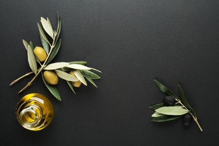 Olio d'oliva e rami di ulivo su fondo nero Archivio Fotografico - 87701299