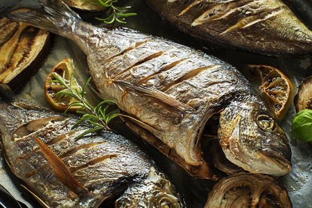 Grilled Gilt-head bream fish with lemon herbs oil vegetables and spices