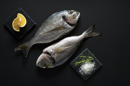 gilt head: Delicious fresh fish gilt-head on dark background. Healthy food diet or cooking concept Stock Photo