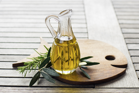 Olive oil with herbs and branch on wooden background