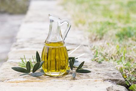 Butelka oliwy z oliwek z ziół i gałęzi w tle przyrody Zdjęcie Seryjne