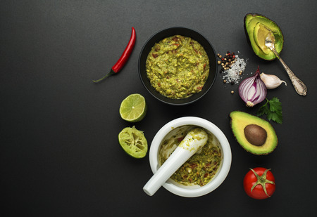 Fresh ingredients with avocado for guacamole sauce on black background