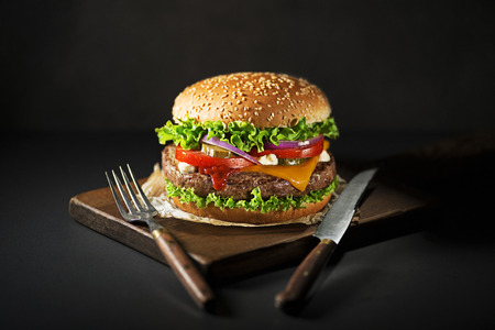 Eating Homemade hamburger or burger with fresh vegetables and cheese
