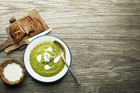 Fresh healthy green soup with cream served on wooden background Stock Photo
