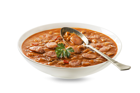 Baked beans stew with tomato sauce and sausage with herbs isolated on white