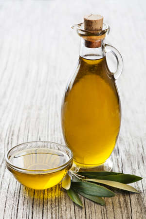 Bottle of Extra virgin healthy Olive oil with leaves close up