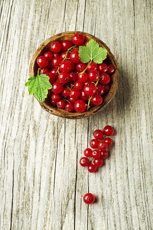 Fresh red currant berries with leaves on wooden background close up