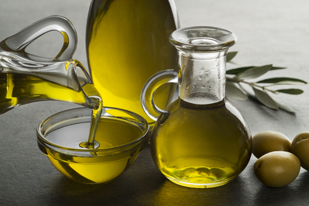 Organic olive oil. Bottle of Extra virgin oil pouring in to glass bowl