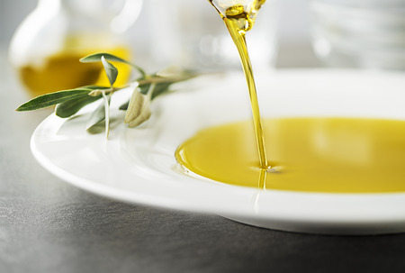 Bottle of healthy virgin olive oil pouring to plate close up 版權商用圖片