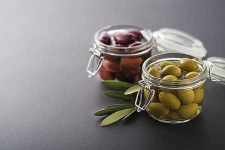 Pickled green and black olives in glass jar with branch leaves close up