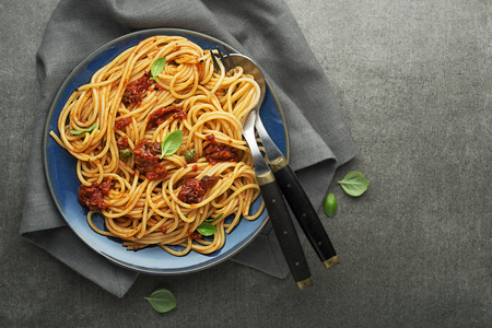 Delicious meal with spaghetti and tomato sauce with basil served on gray background
