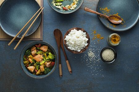 Eating Chinese food with rice, salmon and vegetables Foto de archivo - 129375111