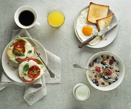 Breakfast served with oatmeal and fruits, mozzarella sandwich and fried egg with bread on table top view. Heathy breakfast food. 写真素材