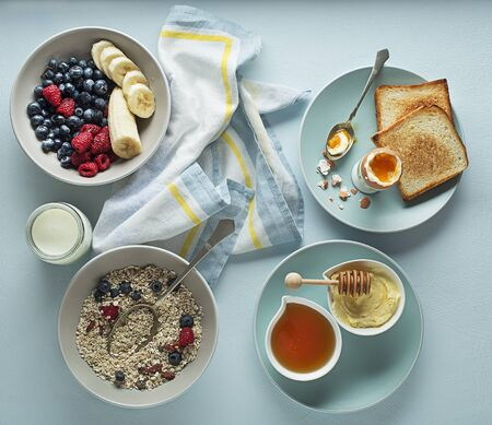 Breakfast served with oatmeal and fruits, boiled egg, honey and butter. Delicious healthy breakfast. Foto de archivo - 129420087