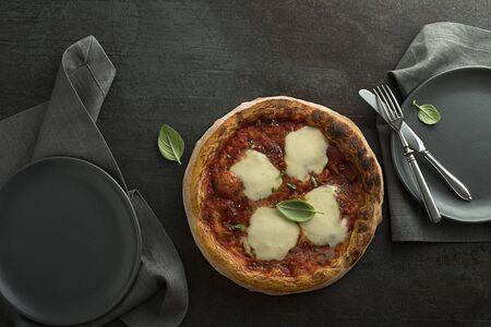 Pizza Margherita served with mozzarella cheese, tomato sauce and fresh basil Foto de archivo - 129420120