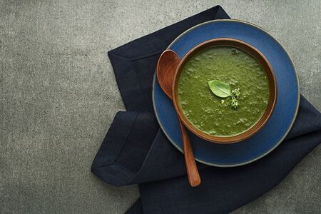 Eating spring healthy meal. Green creamy soup with vegetables and herbs