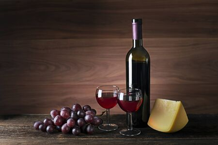 Glasses and bottle of red wine on wooden background 스톡 콘텐츠
