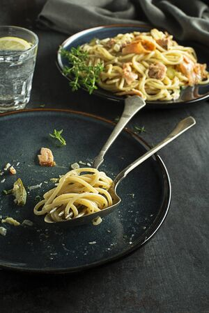 Eating fresh pasta with smoked salmon in cream sauce. Healthy vegetarian meal Foto de archivo - 129831870
