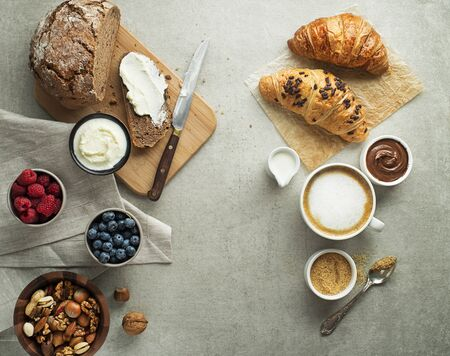 Breakfast served with croissants, coffee, bread, cream cheese and fruits. Delicious healthy breakfast.