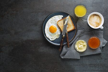Breakfast served with fried egg, jam, butter, coffee and juice on the table top view. Healthy breakfast food Foto de archivo - 131724617