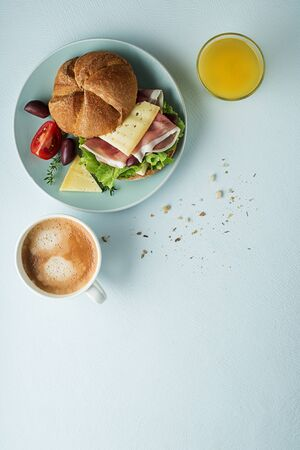 Breakfast served with coffee, juice, sandwich with ham, cheese, tomato and lettuce. Continental delicious healthy breakfast table Stockfoto