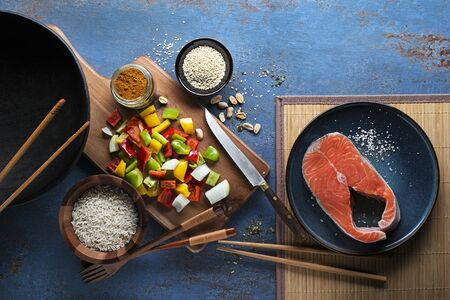 Cooking Chinese food with rice, salmon and vegetables